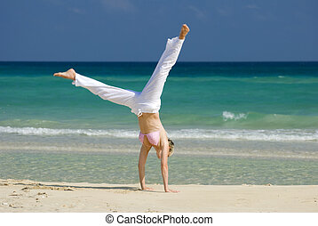 beach - young blond woman making cartwheel on the beach