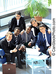 Satisfied proud business team looking at camera and smiling in office