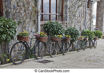 old bicycles with baskets of flowers decorating the wall of...