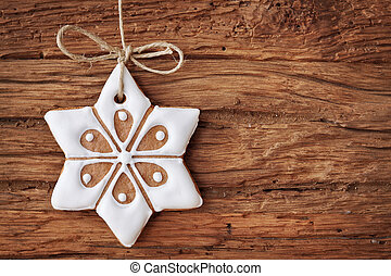 Gingerbread snowflake hanging over wooden background