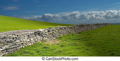 Endless stone wall across the fields of Ireland