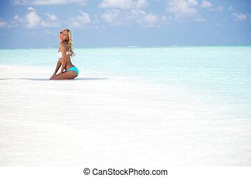 woman in bikini on beach - woman in bikini on sea beach