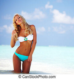 woman in bikini on beach - woman in bikini on sea beach