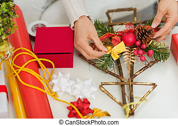 Closeup on female hand making Christmas decorations