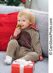 Happy baby in deer suit with Christmas present box eating...