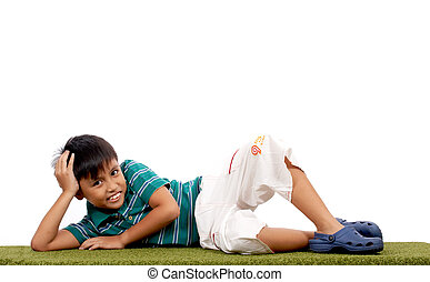 cheerful child lying on a grass over a white background