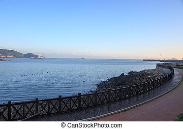 Wooden footpath winding its way along seashore at...
