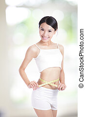 Woman measuring shape of beautiful waist with smile