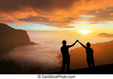 silhouette of Young family happy look sunrise on the top...