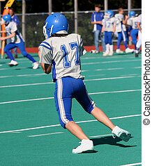 Football Action Play 5 - Teen youth football player in...