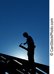 Worker on the roof structure in backlight - Worker...