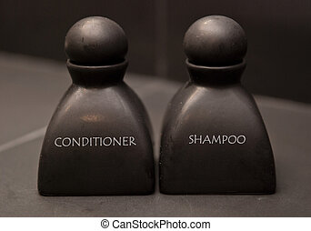 black bottle of shampoo and conditioner