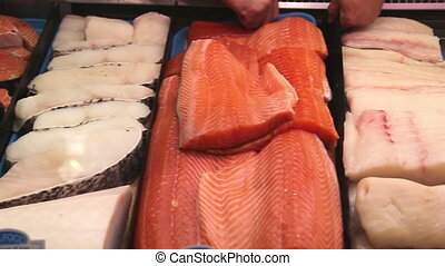 Fish stall in a market - Pan over salmon, white fish, cod,,...