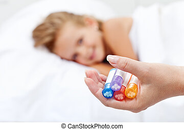 Little girl awaiting homeopathic medication - hand with...