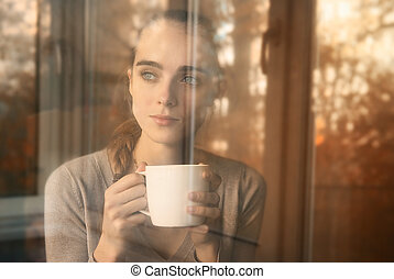 beautiful woman drinking coffee in the morning sitting by...