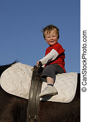 riding little boy - very young boy on a big brown horse