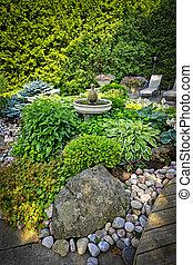 Lush landscaped garden - Lush perennial garden with fountain...