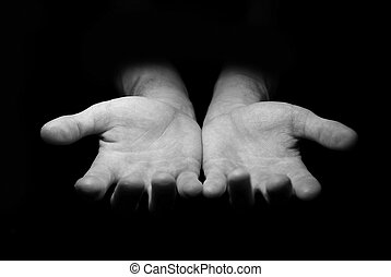 Hands begging alms on a black background