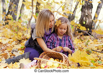 Happy mum and the daughter play autumn park on the fallen...