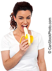 Beautiful young fit girl eating banana isolated on white...