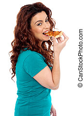 Side pose casual pretty girl enjoying pizza isolated over...