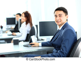 Portrait of a smiling young businessman working on computer at office with his colleagues