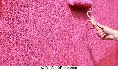 Home renovation - Painting of a pink wall with paint roller