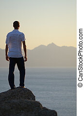 Man stands on a rock and looking at sea