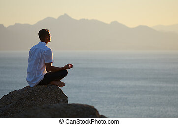 Guy sitting on a rock in the lotus position and looking at...