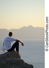 Man sits on a stone - Man sitting on a rock by the sea and...