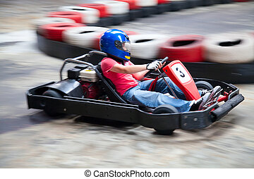 Indoor karting race (rushing kart and safety barriers)