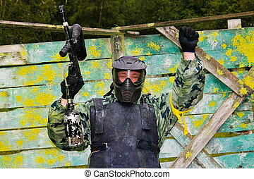 Paintball players in full gear at the shooting range -...
