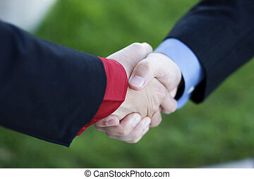 Business Handshake - Two Businessmen seal their deal with a...