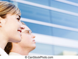 business leaders - profile view of man and woman standing...
