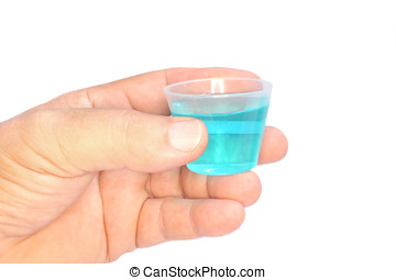 blue mouthwash - close up of hand holding a cup of mint...