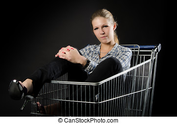 Attractive woman in shopping cart - Attractive young woman...