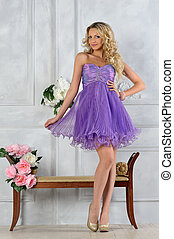 Beautiful blonde woman in lilac dress in luxury interior.