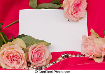 pink roses with pearls strand and blank card background