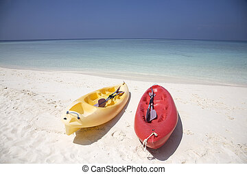 Canoes - Red and yellow canoes left on a sandy beach.