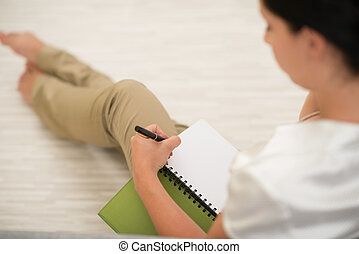 Woman making note in notepad. Rear view