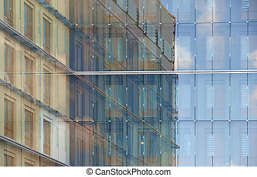 Glass facade with reflection of ajacent buildings