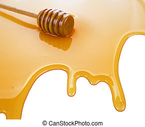 puddle of honey with wooden stick isolated on white...
