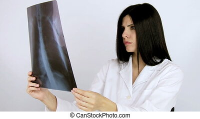 Serious doctor looking xray - Good looking female doctor...