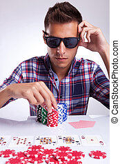 young poker player raises the bet - young poker player with...