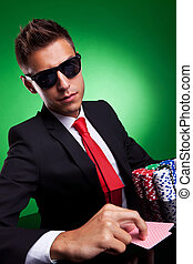 Business man playing with poker face