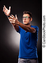 Young casual man holding his hands up, trying to catch or to...