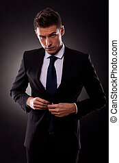 businessman buttoning jacket, getting dressed, on dark...