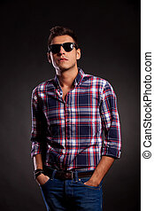 young man standing with both hands in pockets - Casual young...