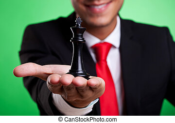 black king of chess in the palm of a young business man