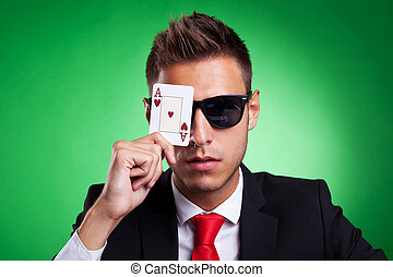 business man covers one eye with an ace of hearts - Young...